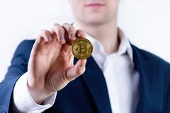 Young business man holding a bitcoin coin. White collar. Cryptocurrency symbol of bitcoin. Money and investment background. Young business man holding a bitcoin royalty free stock photo