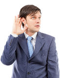 Young business man holding his hand to his ear Stock Photography