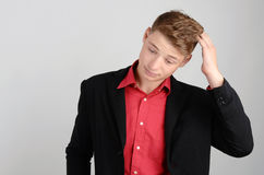 Young business man holding his head down frowning. Man thinking. Royalty Free Stock Photos