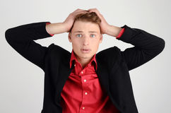 Young business man holding his head frowning with worry. Royalty Free Stock Images
