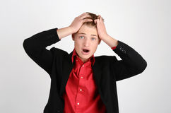 Young business man holding his head frowning with worry screaming. Stock Photography