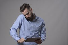 Young business man holding mobile phone on shoulder talking and looking at tablet computer. Over gray studio background. Multitasking concept Royalty Free Stock Photo