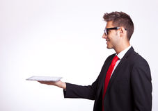 Young business man holding a touch screen pad. Side view of a young business man holding a touch screen pad and looking up above it Stock Photography