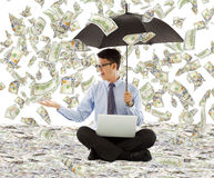 Young business man holding a umbrella with dollar rain Royalty Free Stock Photo