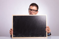 Young business man holds a blank blackboard Stock Photos