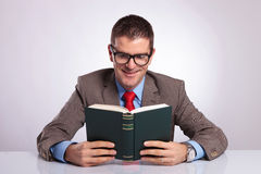 Young business man holds book with both hands Royalty Free Stock Image