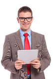 Young business man holds tablet with both hands. Young business man holding his tablet with both hands and smiling for the camera. on a white background Stock Photography