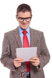 Young business man holds tablet with both hands and reads Stock Image