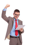 Young business man holds tablet and cheering Royalty Free Stock Images