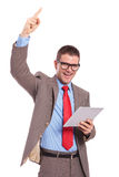 Young business man holds tablet and cheers with finger up Stock Photography