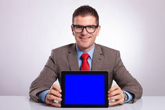 Young business man holds a tablet at his desk Royalty Free Stock Photos