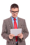 Young business man holds tablet and looks at it Stock Photography