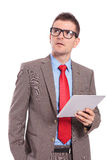 Young business man holds tablet and looks up with hand in pocket Royalty Free Stock Photography