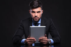 Young business man holds tablet and looks at you Royalty Free Stock Photography