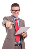 Young business man holds tablet and points at you Royalty Free Stock Image