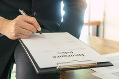 Young Business man insurance agent. Show document contract to the customer at the table in office Stock Photography