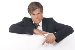 Young business man leaning across a white board Royalty Free Stock Image