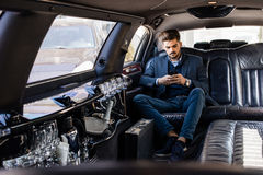 Young business man in limo typing on smart phone Stock Image