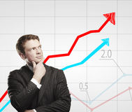 Young business man look at a graph. Royalty Free Stock Images