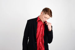Young business man looking down, blowing air in the chest, being hot from emotions. Royalty Free Stock Photos