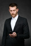 Young business man looking at phone Royalty Free Stock Photography