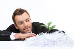 Young business man looking at plant and cut paper. Royalty Free Stock Images