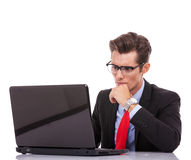 Young business man looking serious at laptop Royalty Free Stock Images