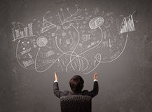Young business man looking at sketches of graphs and symbols. On the wall Stock Images