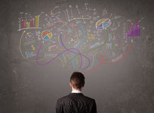 Young business man looking at sketches of graphs and symbols. On the wall Stock Photography