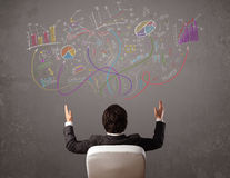 Young business man looking at sketches of graphs and symbols. On the wall Royalty Free Stock Images