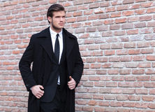 Young business man looking up. Young business man walking by a brick wall and looking up, away from the camera Stock Photo