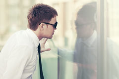 Young business man looking through the window Royalty Free Stock Photography