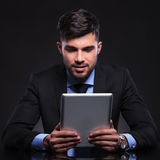 Young business man looks at his tablet Stock Photo