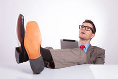 Young business man looks up with feet on desk Stock Image
