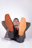 Young business man looks up with hands behind head and feet on d Royalty Free Stock Photography