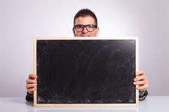 Young business man looks at you from behind blackboard Stock Image