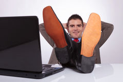 Young business man looks at you with hands behind head. Young business man smiling for the camera while holding his hands behind his head and his feet on the Royalty Free Stock Photo