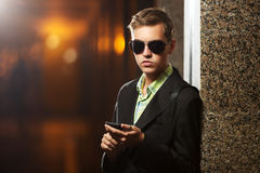 Young business man with a mobile phone standing at the wall Stock Images