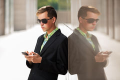 Young business man with a mobile phone standing at the wall Royalty Free Stock Image