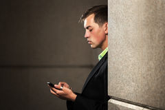 Young business man with a mobile phone at the wall Royalty Free Stock Image