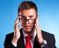 Young business man with a nerd glasses. Funny portrait of a young business man with a nerd glasses trying to put them on Stock Image