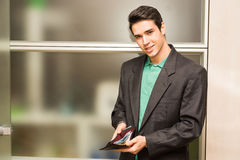 Young business man in office showing full wallet Stock Images