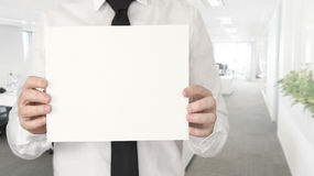 A young business man in the office with a tie holding an empty card Royalty Free Stock Images