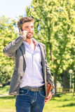 Young business man in the park with smartphone Royalty Free Stock Photos