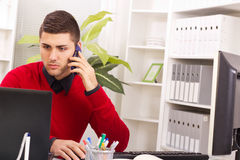 Young business man on phone while using computer Royalty Free Stock Photos