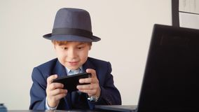 Young business man playing in mobile games at workplace in business office. Little boy in business suit and hat sitting. At office table and playing by mobile stock video