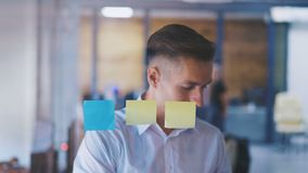 Young business man pointing at sticky notes on a glass in the office, start up development and brainstorming concept stock footage