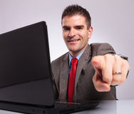 Young business man points at camera while smiling behind laptop Royalty Free Stock Photos
