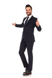 Young business man presenting and making the ok hand sign Stock Photos