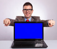 Young business man presents laptop and points with both hands at Stock Photos